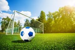 Bola y puertas de fútbol del paso en terreno de juego foto de archivo