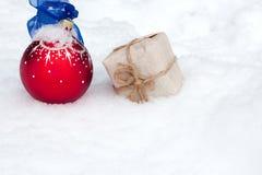 Bola y regalo de la Navidad en nieve Fotografía de archivo
