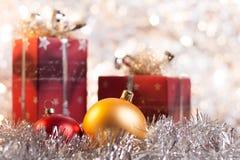 Bola y regalos de la Navidad en fondo ligero Imágenes de archivo libres de regalías
