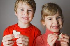 Bolacha do sustento de duas crianças à disposicão e sorriso fotografia de stock