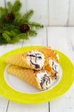Bolachas friáveis do mel sob a forma dos cones, enchidos com o gelado do creme da baunilha do ar com cobertura do xarope de choco Foto de Stock