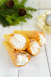 Bolachas friáveis do mel sob a forma dos cones, enchidos com o gelado do creme da baunilha do ar em um fundo branco Fotos de Stock