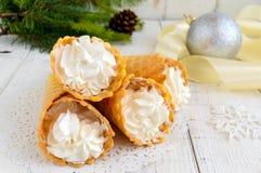 Bolachas friáveis do mel sob a forma dos cones, enchidos com o gelado do creme da baunilha do ar em um fundo branco Imagem de Stock