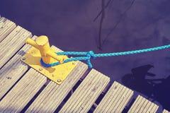 Bolardo amarillo del amarre con la cuerda azul imagen de archivo