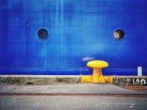 Bolardo amarillo y casco azul foto de archivo