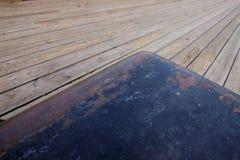 Bolardo de acero que aherrumbra en una nueva cubierta de madera Foto de archivo