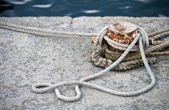 Bolardo de la amarradura con las cuerdas náuticas anudadas fotos de archivo libres de regalías