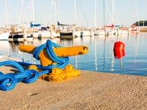 Bolardo del amarre con la cuerda en el embarcadero por el mar Foto de archivo