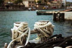 Bolardo del amarre, entrelazado con la cuerda del amarre en el puerto en la bahía imagen de archivo libre de regalías