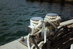 Bolardo del amarre, entrelazado con la cuerda del amarre en el puerto en la bahía imagen de archivo