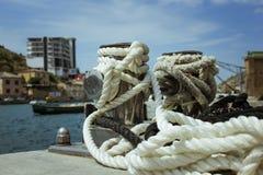 Bolardo del amarre, entrelazado con la cuerda del amarre en el puerto en la bahía foto de archivo libre de regalías