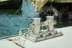 Bolardo del amarre, entrelazado con la cuerda del amarre en el puerto en la bahía imagenes de archivo
