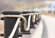 Bolardos con las cuerdas en un muelle para el cercado decorativo Foto de archivo