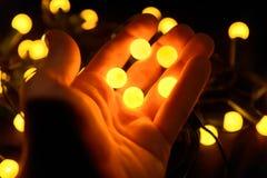 Bolas amarelas brilhantes nas mãos de um homem imagens de stock