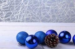 Bolas azuis do Natal, e cone de abeto em um fundo de madeira imagens de stock