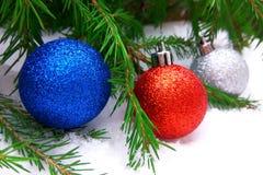 Bolas azuis, vermelhas e de prata do ano novo com a árvore de abeto verde no fundo nevado imagem de stock