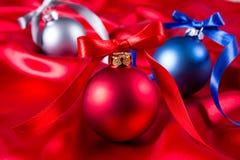 Bolas azuis, vermelhas e de prata do Natal em um pano de seda Imagens de Stock Royalty Free