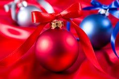 Bolas azuis, vermelhas e de prata do Natal em um pano de seda Imagens de Stock