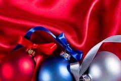 Bolas azuis, vermelhas e de prata do Natal em um pano de seda Fotografia de Stock