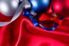 Bolas azuis, vermelhas e de prata do Natal em um pano de seda Imagem de Stock
