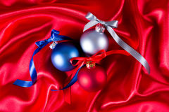 Bolas azuis, vermelhas e de prata do Natal em um pano de seda Imagem de Stock Royalty Free
