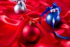 Bolas azuis, vermelhas e de prata do Natal em um pano de seda Fotos de Stock