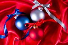 Bolas azuis, vermelhas e de prata do Natal em um pano de seda Fotografia de Stock Royalty Free