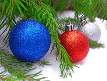 Bolas azules, rojas y de plata del Año Nuevo con el árbol de abeto verde en fondo nevoso foto de archivo libre de regalías