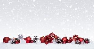 Bolas blancas y rojas de la Navidad con los presentes de Navidad en fila aislados en nieve Imagen de archivo libre de regalías