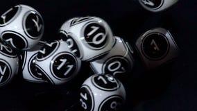 Bolas blancos y negros de la lotería en una cámara lenta de la máquina metrajes