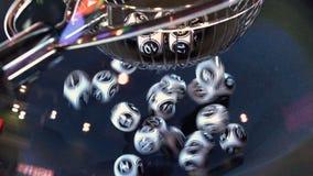 Bolas blancos y negros de la lotería en una máquina giratoria del bingo 4K metrajes