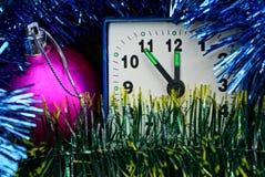 Bolas bonitas coloridas do Natal e um despertador quadrado pequeno Foto de Stock