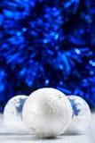 Bolas brancas e de prata do Natal na obscuridade - fundo azul do bokeh com espaço para o texto Imagem de Stock