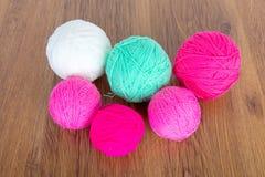 Bolas brilhantes do fio acrílico em uma tabela de madeira needlework Faça malha e fazer crochê Tendências da forma Imagens de Stock