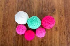 Bolas brilhantes do fio acrílico em uma tabela de madeira needlework Faça malha e fazer crochê Tendências da forma Fotografia de Stock Royalty Free