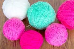 Bolas brilhantes do fio acrílico em uma tabela de madeira needlework Faça malha e fazer crochê Tendências da forma Fotos de Stock