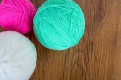 Bolas brilhantes do fio acrílico em uma tabela de madeira needlework Faça malha e fazer crochê Tendências da forma Fotos de Stock Royalty Free