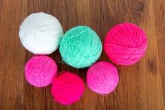 Bolas brilhantes do fio acrílico em uma tabela de madeira needlework Faça malha e fazer crochê Tendências da forma Fotografia de Stock
