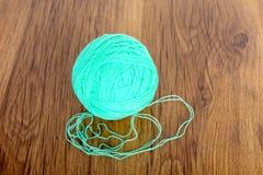 Bolas brilhantes do fio acrílico em uma tabela de madeira needlework Faça malha e fazer crochê Tendências da forma Foto de Stock Royalty Free