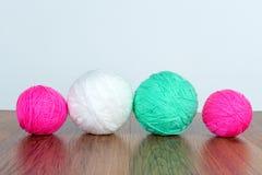 Bolas brilhantes do fio acrílico em uma tabela de madeira needlework Faça malha e fazer crochê Tendências da forma Foto de Stock