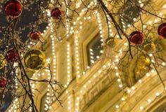 Bolas brilhantes vermelhas douradas em um ramo contra o contexto da casa decorada com uma festão de incandescência, uma noite Foto de Stock