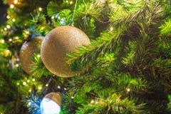 Bolas brillantes de oro que cuelgan en el árbol de navidad Foto de archivo