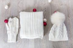 Bolas cercanas accesorias hechas punto del árbol del Año Nuevo del tiempo frío en la tabla Sombrero blanco, fondo de madera gris  Imagen de archivo libre de regalías