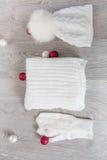 Bolas cercanas accesorias hechas punto del árbol del Año Nuevo del tiempo frío en la tabla Sombrero blanco, fondo de madera gris  Imagenes de archivo