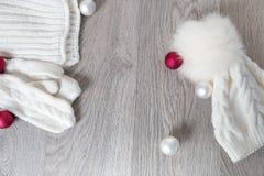 Bolas cercanas accesorias hechas punto del árbol del Año Nuevo del tiempo frío en la tabla Sombrero blanco, fondo de madera gris  Imágenes de archivo libres de regalías