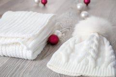 Bolas cercanas accesorias hechas punto del árbol del Año Nuevo del tiempo frío en la tabla Sombrero blanco, fondo de madera gris  Fotos de archivo libres de regalías