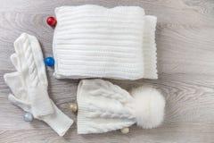Bolas cercanas accesorias hechas punto del árbol del Año Nuevo del tiempo frío en la tabla Sombrero blanco, fondo de madera gris  Imagen de archivo