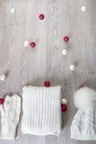 Bolas cercanas accesorias hechas punto del árbol del Año Nuevo del tiempo frío en la tabla Sombrero blanco, fondo de madera gris  Fotografía de archivo