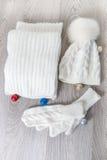 Bolas cercanas accesorias hechas punto del árbol del Año Nuevo del tiempo frío en la tabla Sombrero blanco, fondo de madera gris  Foto de archivo libre de regalías