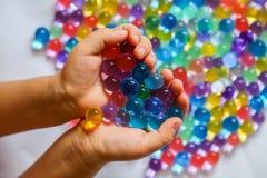 Bolas coloreadas del hidrogel en palmas del ` s de los niños Foto de archivo libre de regalías